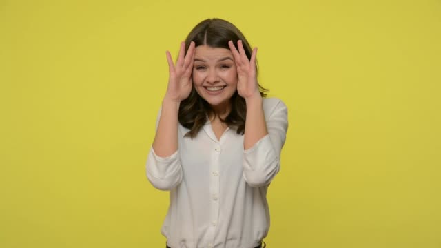 donna adorabile felice con i capelli bruni in camicetta che si apre e si copre il viso con le mani, giocando a nascondino - flirtare video stock e b–roll