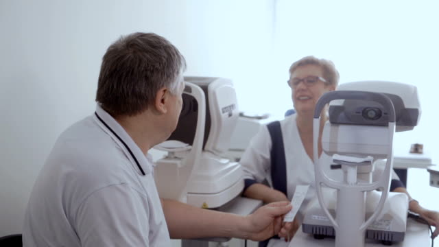 Happy adult man in ophthalmological clinic Doctor talks with patient after the procedure of checking eyesight. The man look on the doctor sitting near optical modern equipment. eye exam stock videos & royalty-free footage