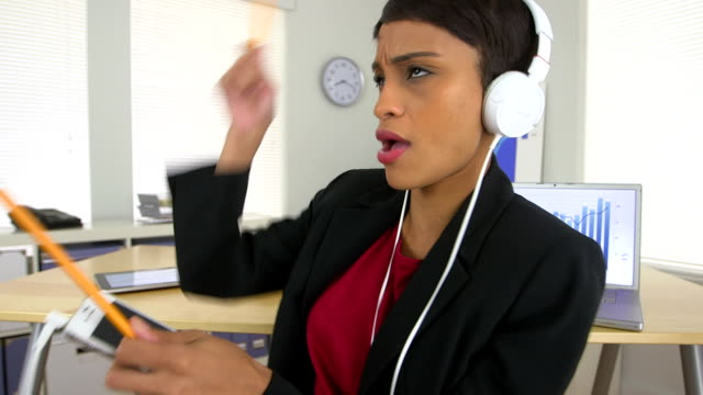 Happy African American business woman listening to music at work video