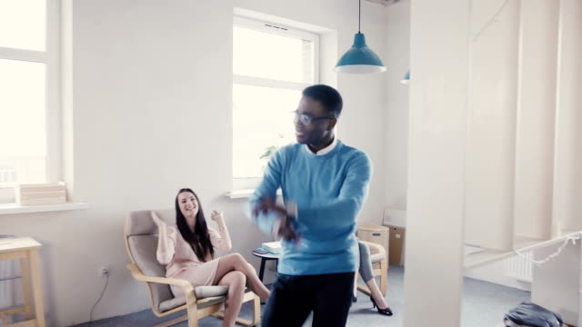 Happy African American businessman celebrating promotion with funny dance walk. Successful boss in modern office 4K Happy African American businessman celebrating promotion with funny silly dance walk. Successful boss in modern multiethnic healthy office 4K. Millennial manager excited over career achievement. genius stock videos & royalty-free footage