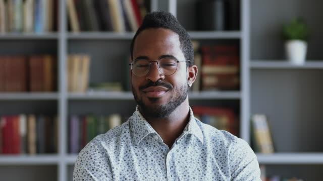 vídeos y material grabado en eventos de stock de feliz hombre de negocios afroamericano mirando la cámara en la oficina, retrato - hombres