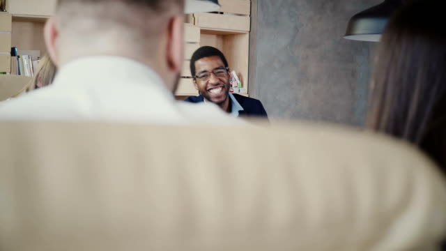 Happy African American company boss laughs at multiethnic office meeting, then goes serious again in trendy coworking 4K video