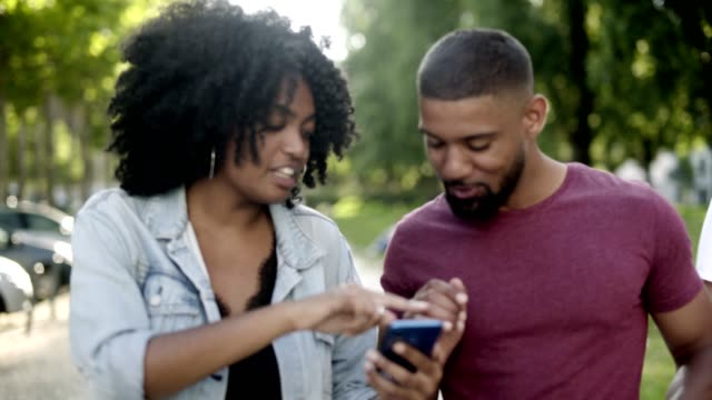Happy African American couple looking at smartphone