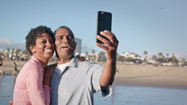 happy african american couple take selfie on beach - retirement stock videos and b-roll footage