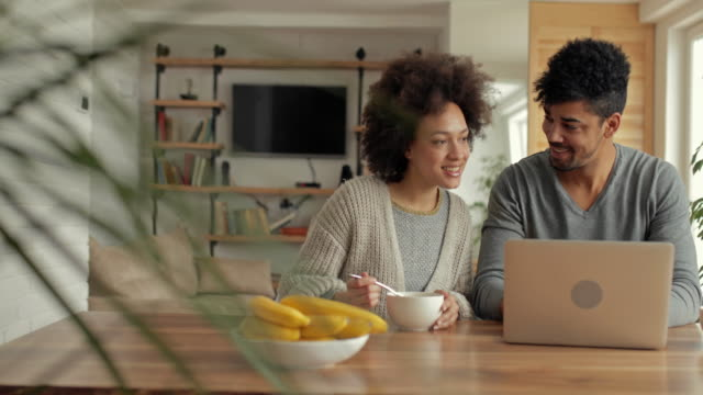 Happy African American couple using laptop and having fun while watching something funny on the Internet. video