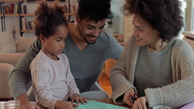 Happy African American family having fun while making something creative with paper and scissors. video
