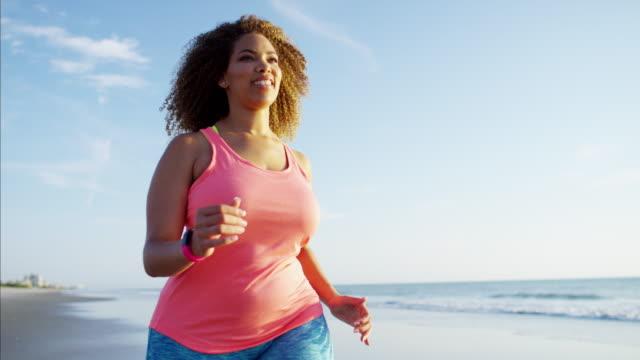 Happy African American female speed walking on beach