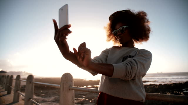 Happy African American hipster teen girl at the beach taking a selfie on her phone video