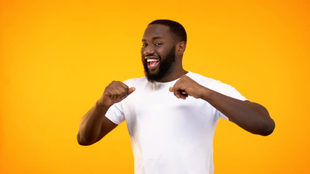 happy african american man dancing and singing, isolated on yellow background - vincere video stock e b–roll