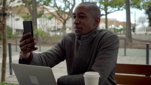 vídeos de stock e filmes b-roll de happy african american man having video chat via smartphone - esplanada portugal