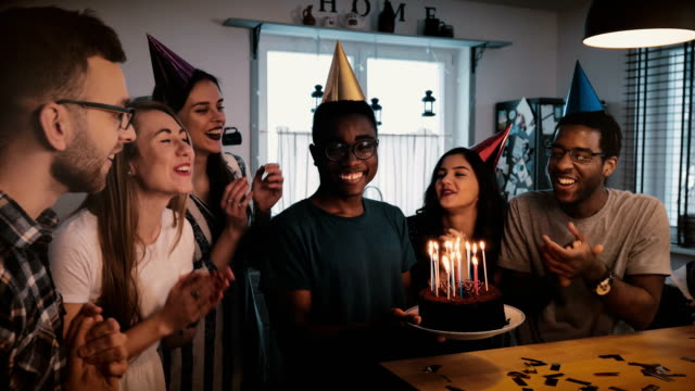 happy african american man holding birthday cake, dancing and celebrating at multiethnic party with friends slow motion - birthday stock videos and b-roll footage