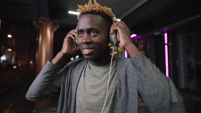 vídeos y material grabado en eventos de stock de feliz hombre afroamericano usando auriculares en lugar subterráneo nocturno - basement