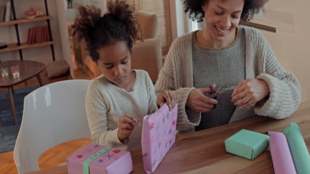 Happy African American mother and daughter wrapping presents together at home. Young African American mother and daughter having fun while wrapping presents together at home. wrapped stock videos & royalty-free footage