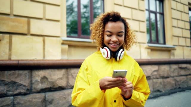 stockvideo's en b-roll-footage met gelukkig african american student is het gebruik van smartphone browsen of sms'en vrienden permanent buiten in de straat van moderne stad hoofdtelefoon dragen en lachend. - {{asset.href}}