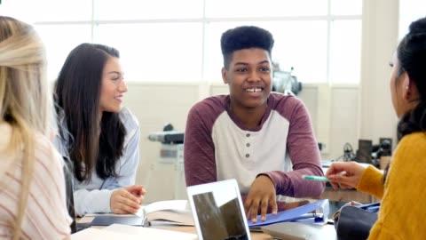 vídeos y material grabado en eventos de stock de feliz niño afroamericano adolescente disfruta de tiempo con el grupo de estudio - estudiante