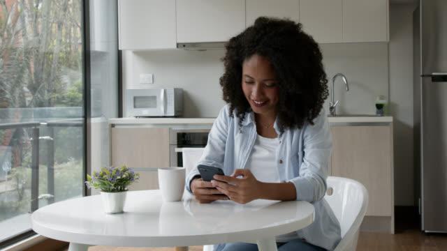 그녀의 스마트 폰에 응용 프로그램을 사용하여 집에서 행복한 아프리카 계 미국인 여성과 커피 한 잔을 마시는 - 성인 전용 스톡 비디오 및 b-롤 화면