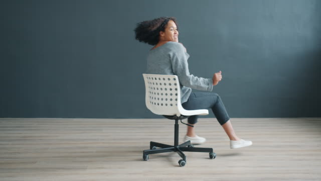 Happy African American woman spinning sitting on office chair dancing having fun