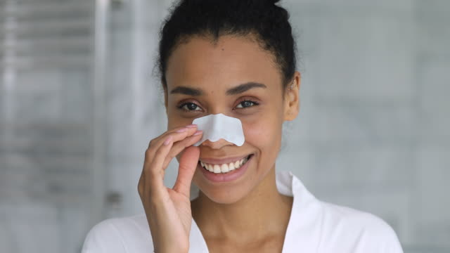 Happy african american woman using nose cleansing strip.
