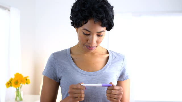 Happy African American woman with pregnancy test video