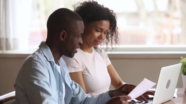 Happy african american young couple paying bills online at home Happy african american young couple paying bank loan bills online at home, millennial black husband holding papers doing paperwork payment with wife using laptop planning budget sit at desk at home bills and taxes stock videos & royalty-free footage