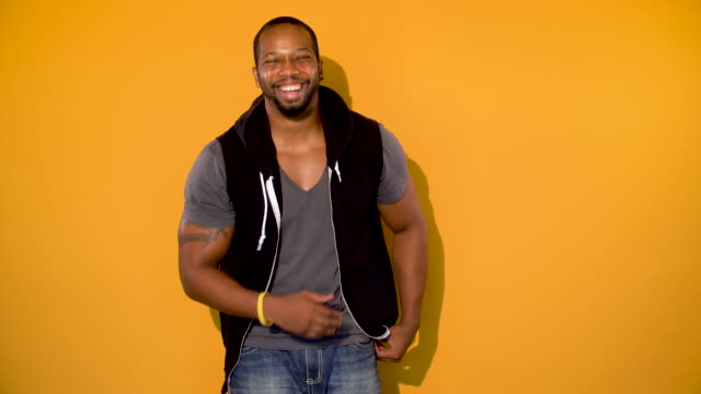 Happy African American Young Man Young in shape African American male laughing on a yellow background. background color stock videos & royalty-free footage