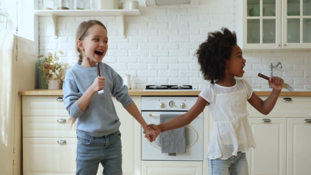 Happy african and caucasian kids stepsisters singing, dancing in kitchen