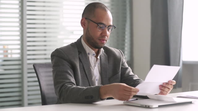 Happy african businessman read mail letter excited by good news Happy african american businessman winner open envelope read mail letter excited by good news got new job hired promoted, overjoyed by loan approval, receiving bill salary celebrating taxes refund goal post stock videos & royalty-free footage