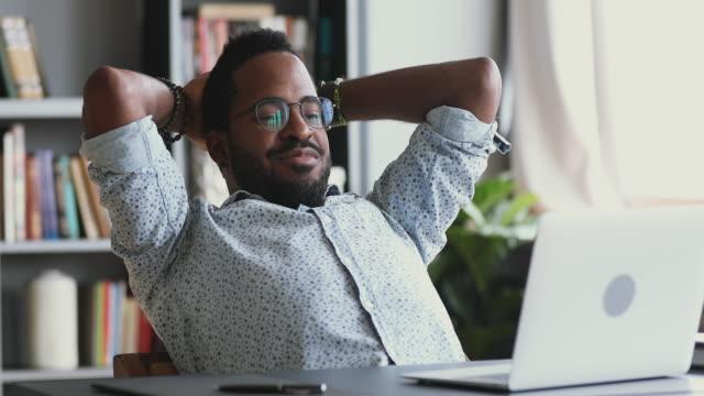 직장에서 노트북에 비디오를보고 편안한 행복한 아프리카 사업가 - black friday 스톡 비디오 및 b-롤 화면