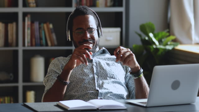happy african businessman wear headphones listening music at work desk - cuffie wireless video stock e b–roll