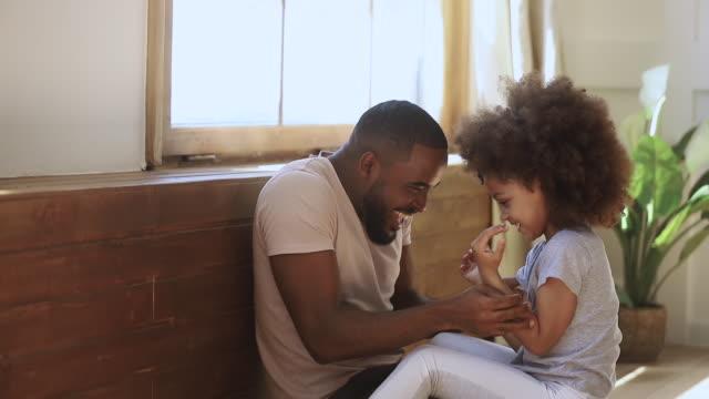 vídeos de stock, filmes e b-roll de filha africana feliz da criança e pai que jogam cócegas em casa - fathers day