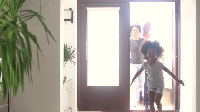 Happy african child girl with parents running into new house