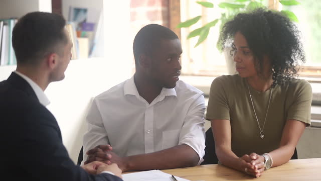 Happy african couple buying new house signing contract get keys Happy african american couple first time home buyers owners renters tenants renting buying new house signing rental sale purchase contract handshaking realtor get keys make real estate mortgage deal financial building stock videos & royalty-free footage