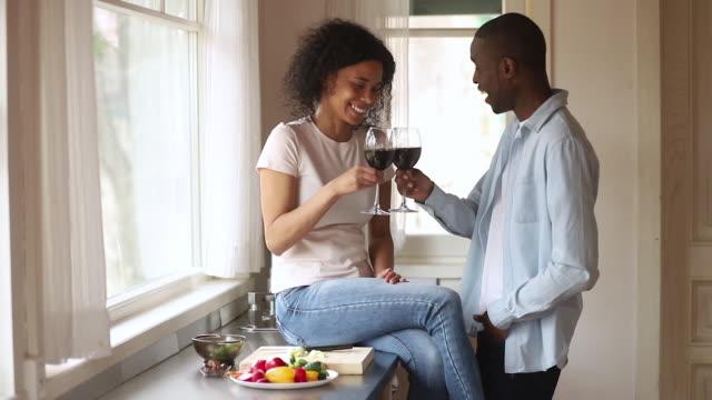vídeos de stock, filmes e b-roll de pares africanos felizes que clinking os vidros falam a ligação do riso na cozinha - vinho