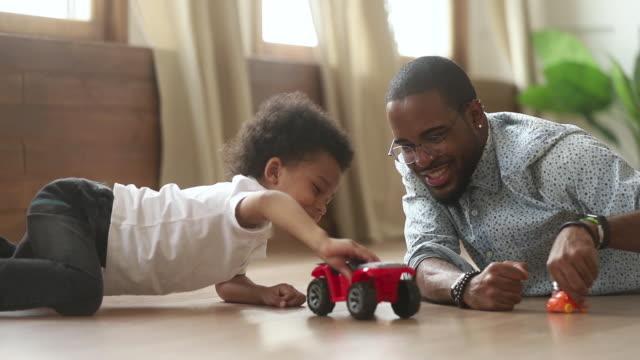 glücklich afrikanische niedlichen kleinen sohn spielen spielzeug autos mit papa - person gemischter abstammung stock-videos und b-roll-filmmaterial