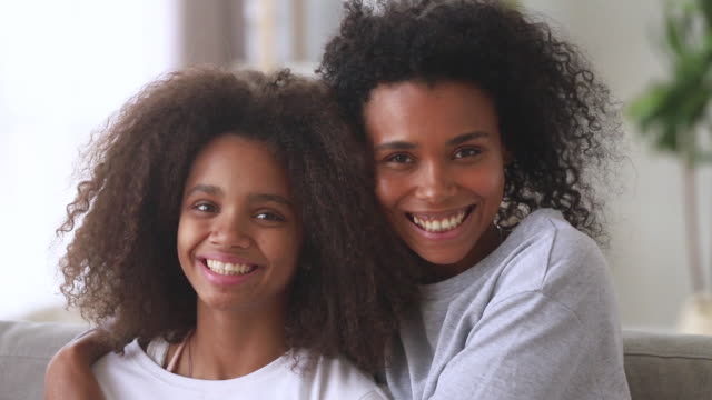 十代の娘が絆を抱きしめる幸せなアフリカの家族のお母さん、肖像画 - 兄弟姉妹点の映像素材/bロール