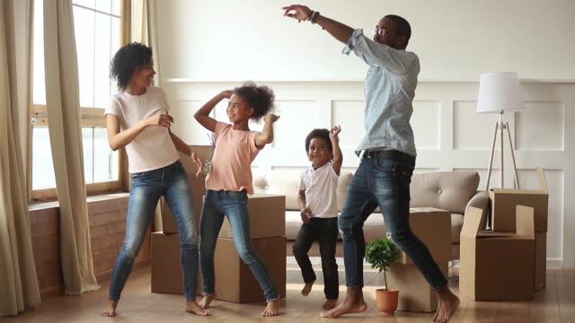 lycklig afrikansk familj föräldrar och barn dansar firar flyttdagen - flyttlådor bildbanksvideor och videomaterial från bakom kulisserna