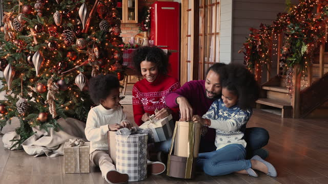 Happy African family with kids opening gift boxes celebrating Christmas