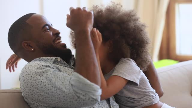 vídeos y material grabado en eventos de stock de feliz padre africano y su hija su hija cosquillas sentarse en el sofá - recuerdos