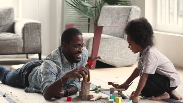Happy african father and kid son playing toys at home