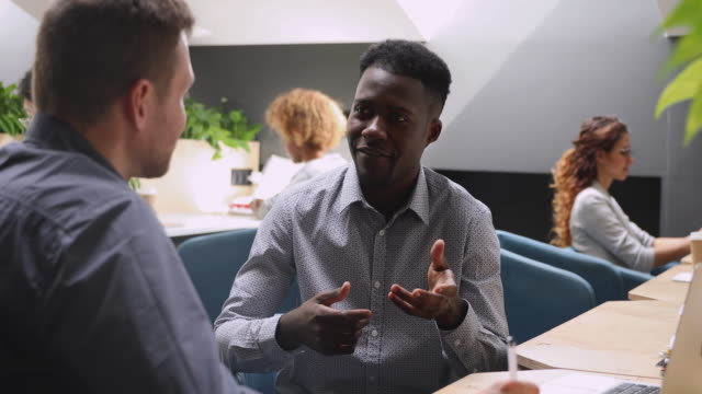 Happy african male executive talking to caucasian colleague in office