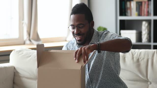 mutlu afrikalı adam müşteri açık karton kutu paketi almak - sipariş vermek stok videoları ve detay görüntü çekimi