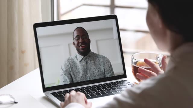 vídeos de stock e filmes b-roll de happy african man talks with woman makes videocall on laptop - envolvimento dos funcionários