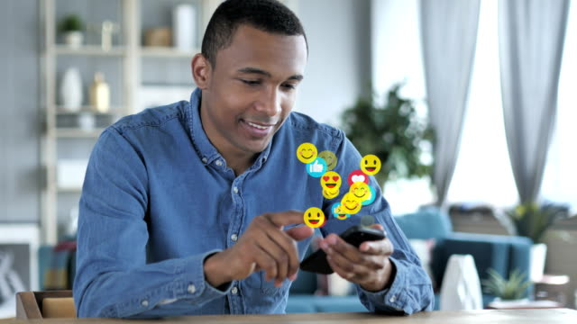 glücklicher afrikanischer mann mit smartphone, emojis, smileys und likes - smiley stock-videos und b-roll-filmmaterial