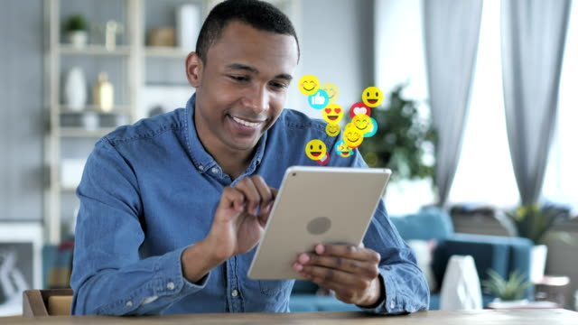vídeos de stock e filmes b-roll de happy african man using tablet, emojis, smileys and likes - mensagens online