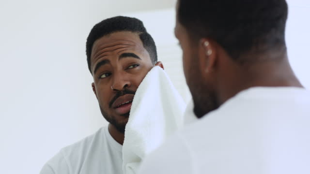 Happy african man wiping face with towel looking in mirror