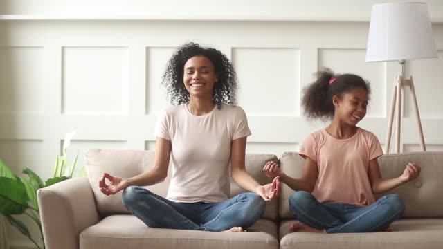 Happy african mom teaching kid daughter doing yoga at home Happy family mindful african mom teaching cute funny kid daughter doing yoga exercise at home, calm healthy mixed race mother and little girl sitting in lotus pose on sofa meditating together mindfulness stock videos & royalty-free footage