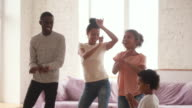 istock Happy african parents and cute funny kids dancing at home 1172465813