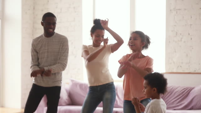 Happy african parents and cute funny kids dancing at home