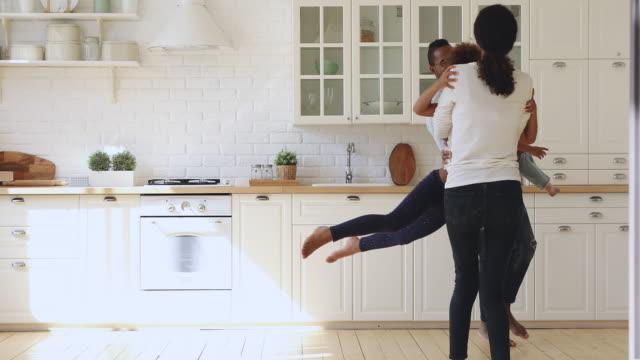 Happy african parents holding kids having fun dancing in kitchen