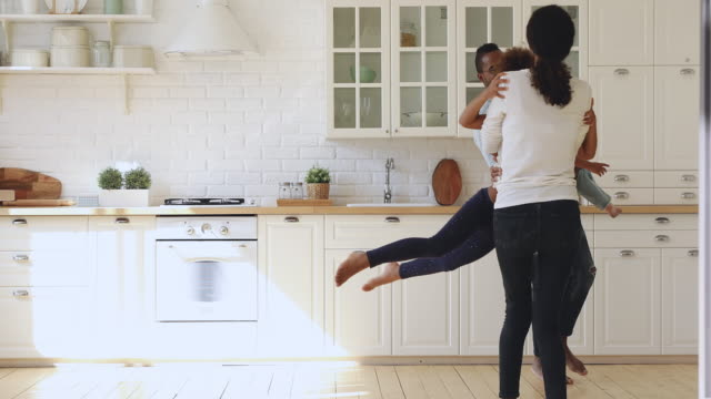 happy african parents holding kids having fun dancing in kitchen - due genitori video stock e b–roll